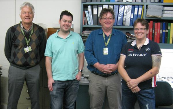 Quatre personnes debout dans un laboratoire de minéralogie.