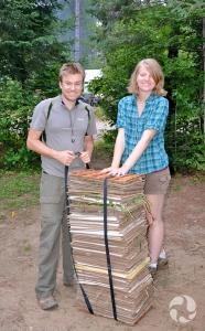 Shaleen Humphreys et Jeff Saarela debout près d'une pile haute jusqu'à mi-corps de plantes aplaties dans des feuilles.