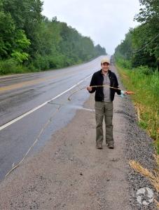 Jeff Saarela, debout près de la route, tenant la longue tige ligneuse d'un roseau commun.