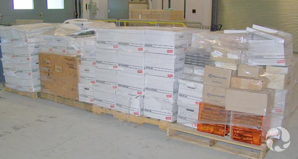 Piles de boîtes contenant la collection Steele reposant sur des palettes de bois.