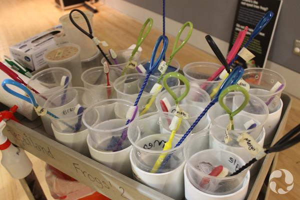 Des verres en polystyrène contenant chacun une brosse à dents et un petit filet sont disposés sur le dessus d'un chariot.