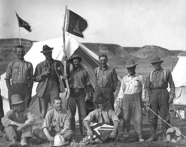 Neuf hommes debout et assis posent pour une photo dans un campement en Alberta.