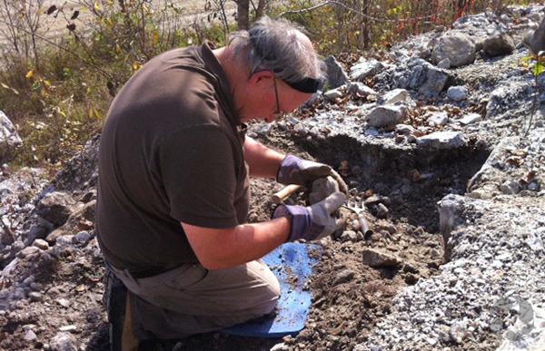 Un homme agenouillé sur le sol examine une roche qu'il tient dans ses mains.