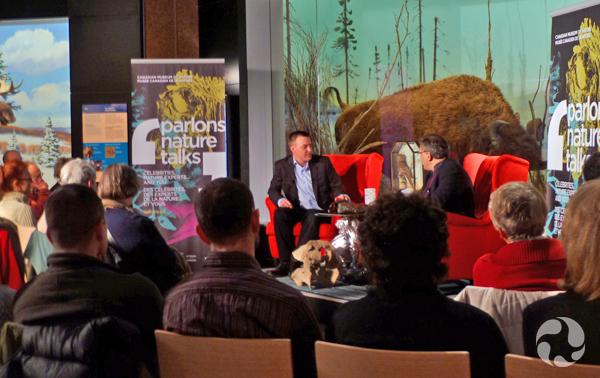 Deux hommes discutent, assis devant des spectateurs, dans la Galerie des mammifères au Musée canadien de la nature.