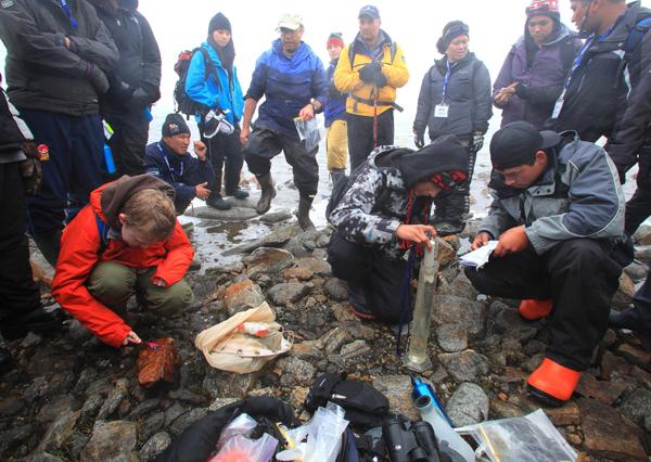 Paul Hamilton supervise des élèves qui prélèvent des échantillons d'eau d'un ruisseau arctique.