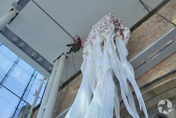La toile de la méduse, dégonflée, est hissée par des câbles dans le lanternon.