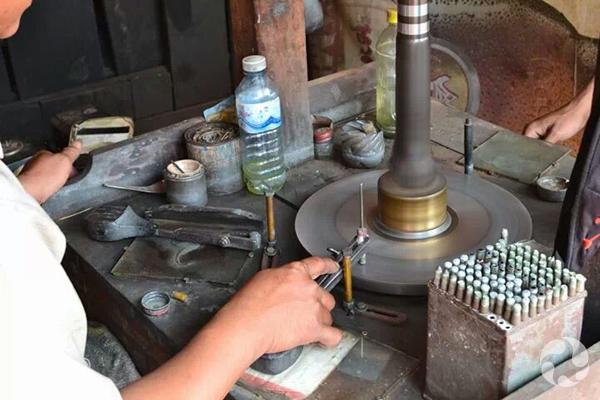 Un tailleur de gemmes, assis devant son appareil,  tient une tige sur laquelle se trouve un zircon.