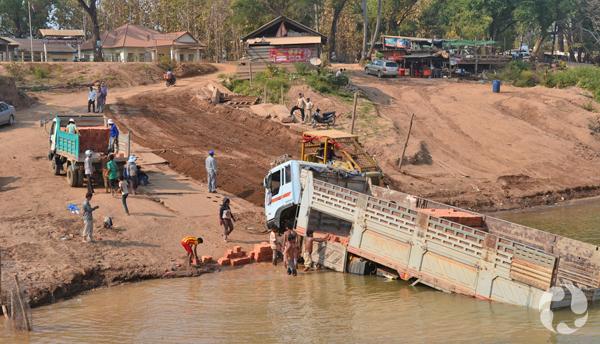 Un long camion partiellement submergé le long des rives du fleuve Mékong.