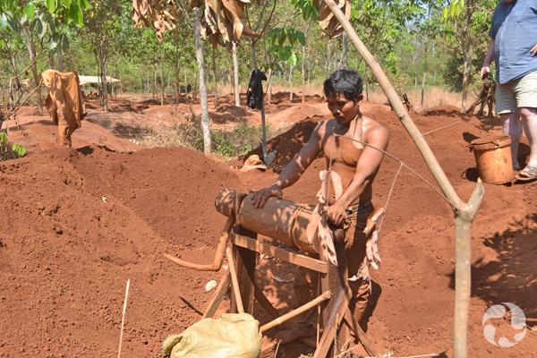 Un mineur de zircons debout près d'une machine de bois utilisée pour hisser les seaux des profondeurs de la mine.