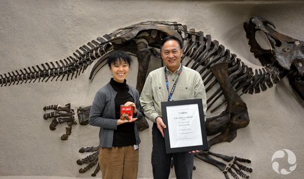 Un homme et une femme debout devant un fossile en bas-relief. L'homme tient un certificat dans ses mains et la femme, une conserve de tomate.