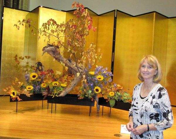 Une femme près d'un arrangement floral ikebana.