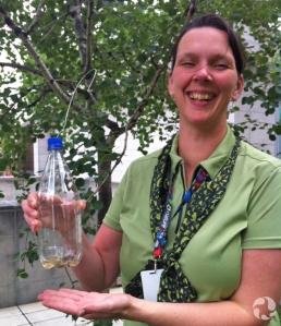 Une femme montre une trappe à insectes volants fabriquée à partir d'une bouteille en plastique et suspendue à un arbre.