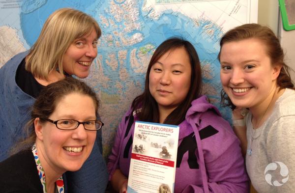 Quatre femmes debout devant une carte géographique de l'Arctique accrochée au mur.