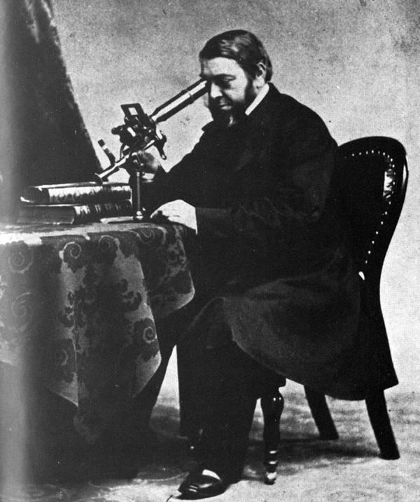 Photo d'archives : un homme assis devant une table regarde dans un microscope, au milieu du XIXe siècle.