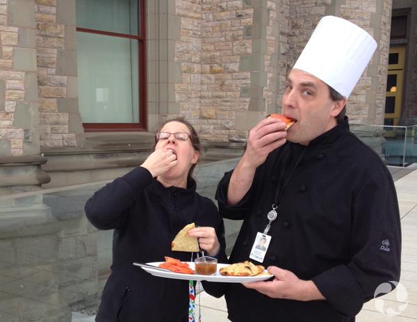 Un homme portant une toque de chef et tenant une assiette à la main déguste de la nourriture en compagnie d'une femme, à l'extérieur du Musée.