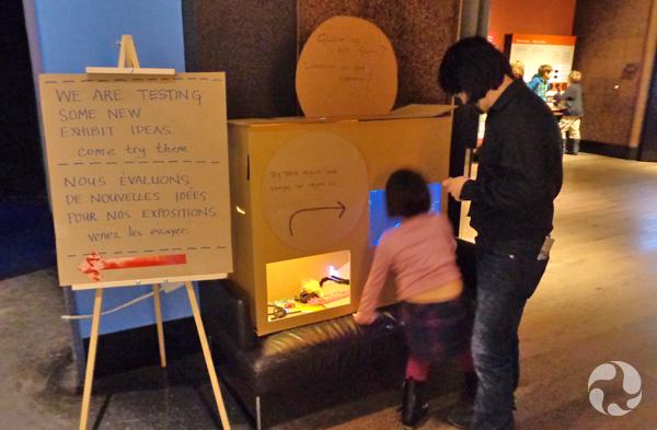 Un adulte et un enfant examinent une maquette en carton d'une installation interactive.