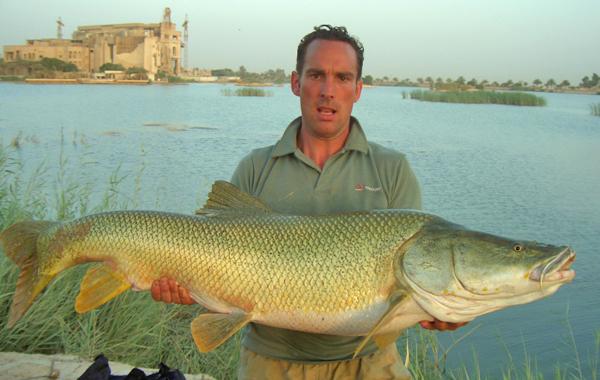 Un soldat en Iraq tient un gros poisson qu'il a attrapé.
