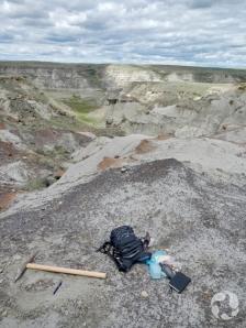 Sac à dos et pic déposés sur le sol dans un site fossilifère surplombant la rivière Saskatchewan Sud.