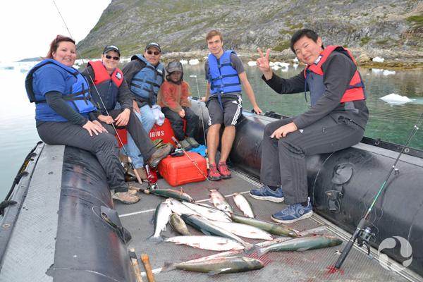 Paula et des participants assis dans le Zodiac avec les poissons qu'ils ont pêchés.