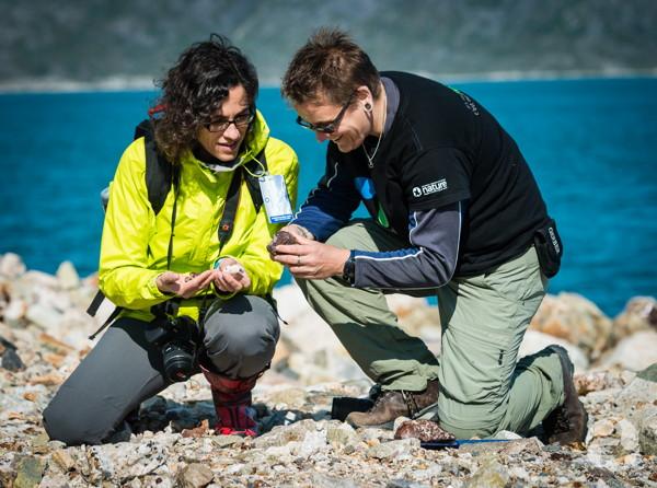 Caroline et un minéralogiste du musée examinent des roches sur une plage.
