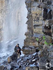 Un homme aux pieds d'une chute en train de collecter des mousses.