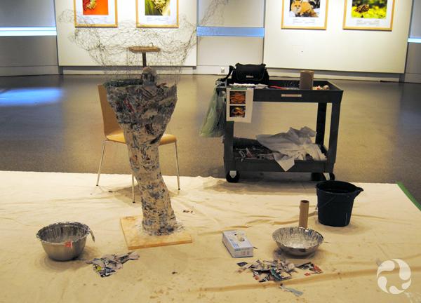 Une sculpture en treillis métallique partiellement recouverte de papier mâché et installée sur une bâche dans une galerie.