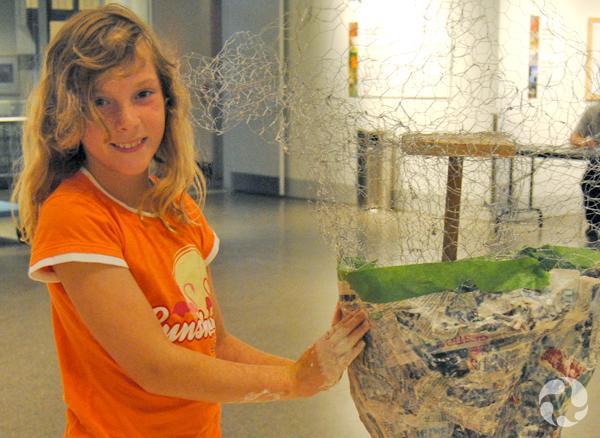 Une jeune fille applique du papier mâché sur une sculpture en treillis métallique.