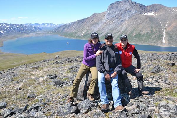 Paula Piilonen et deux participants posent au sommet d'un pic surplombant le fjord.