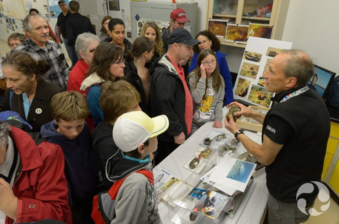 Des gens se massent près d'une table pour écouter un scientifique parler de la biodiversité des moules.