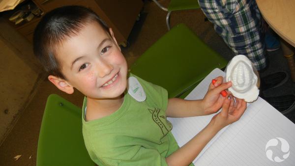 Un jeune garçon prépare un moule de trilobite.