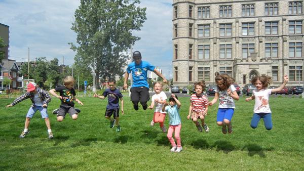 Huit enfants et leur moniteur s'amusent à faire des sauts sur le terrain ouest du Musée.