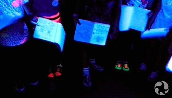 Des carnets forment des taches claires sous une lumière ultraviolette.