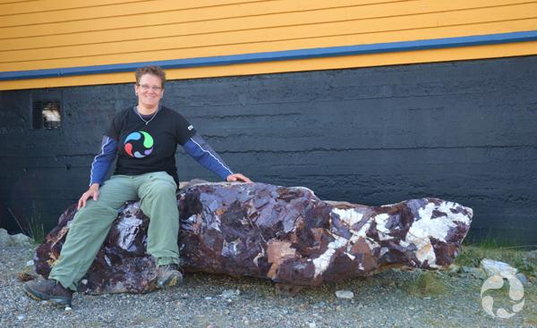 Paula Piilonen, assise sur un gros morceau de minerai contenant des cristaux de cryolite et de sidérose.