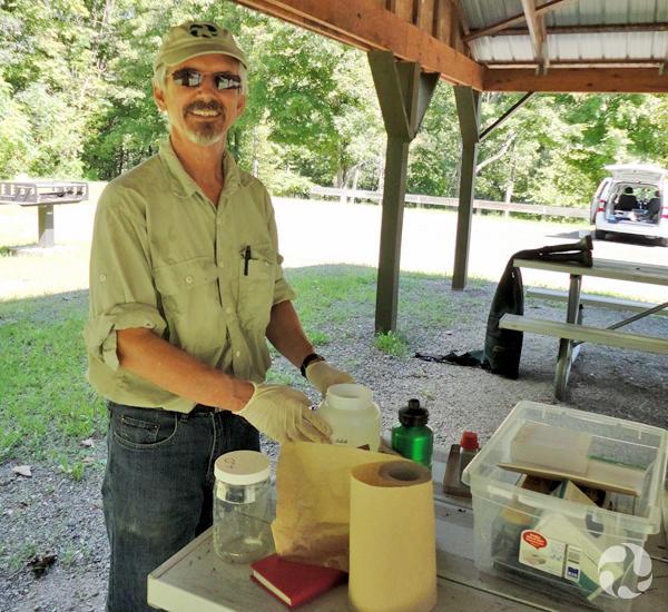 Claude Renaud debout près d'une table sur laquelle on trouve l'équipement utilisé pour traiter des spécimens de lamproies.