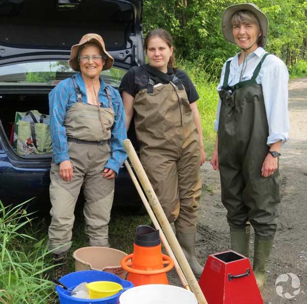 Trois femmes vêtues de pantalons imperméables, et munies de sceaux et de filets.