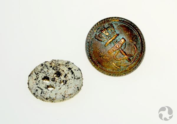 Un bouton blanc à quatre trous et un autre de métal foncé.