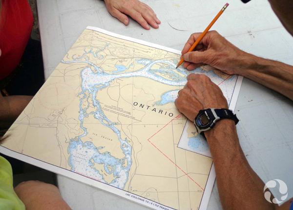Les mains d'une personne qui écrit sur une carte topographique.