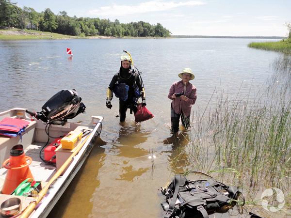 Un homme en habit de plongée et une femme portant des bottes se tiennent dans l'eau peu profonde, près d'un bateau amarré.