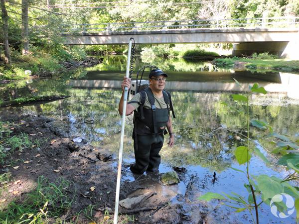 Un homme en bottes-pantalons debout dans la vase de la rivière Saw Kill.