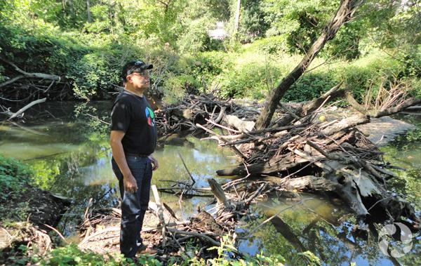 Un homme debout près d'un embâcle le long de la rivière Saw Mill.
