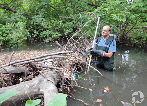 Un homme en bottes-pantalons debout près d'un autre embâcle au ruisseau Tibbetts.