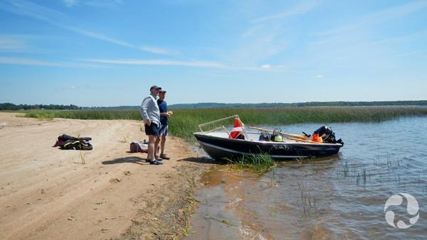 Deux hommes debout près d'une chaloupe à moteur, au bord d'une rivière.