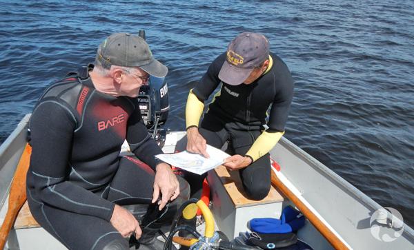 Deux hommes assis dans un bateau en combinaison de plongée sous-marine regardent une carte.