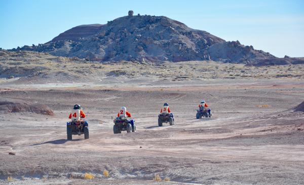Quatre personnes conduisent des véhicules tout-terrain pour s'aventurer dans le désert.