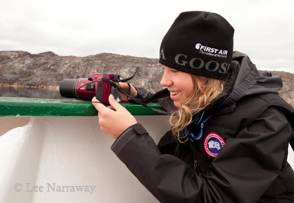 Alana Krug-Macleod tient un appareil-photo et se penche sur le bord d'un navire lors d'un voyage en Antarctique.