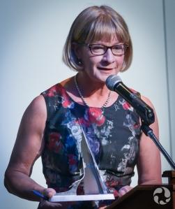 La membre du jury Shelley Ambrose debout près du podium tenant une sculpture.