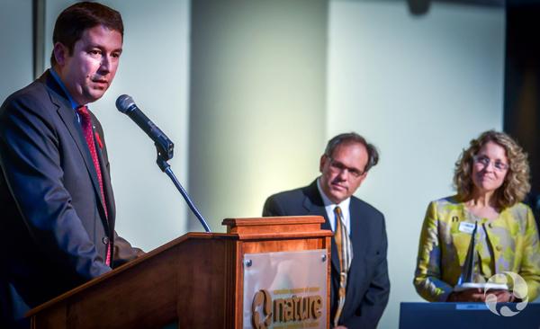 Le lauréat Hugo d'Amours, de Cascades inc., prononce une allocution au podium pendant que Meg Beckel et l'animateur Ivan Semeniuk observent la scène.