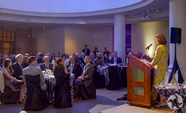 Vue panoramique des invités assis aux tables avec Meg Beckel au podium.