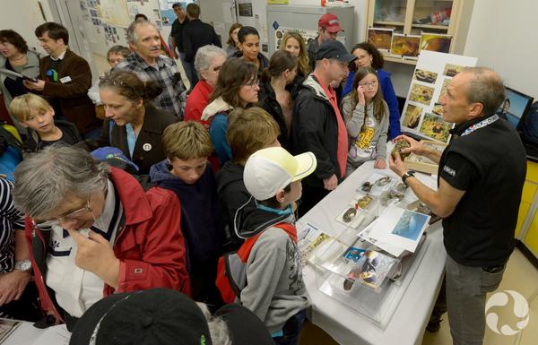 Le scientifique du musée André Martel, Ph. D., debout derrière une table pour montrer des moules aux nombreux visiteurs lors des Portes ouvertes.