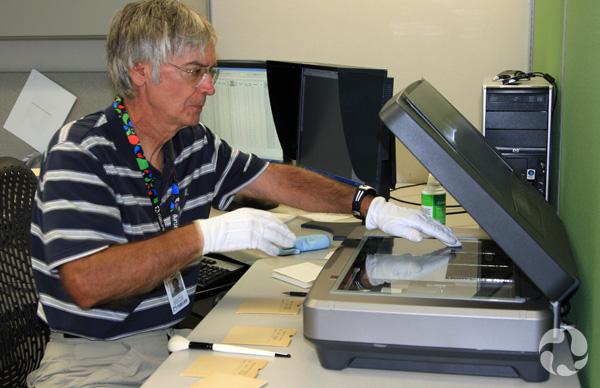 Un homme numérise des photos sur plaque de verre.